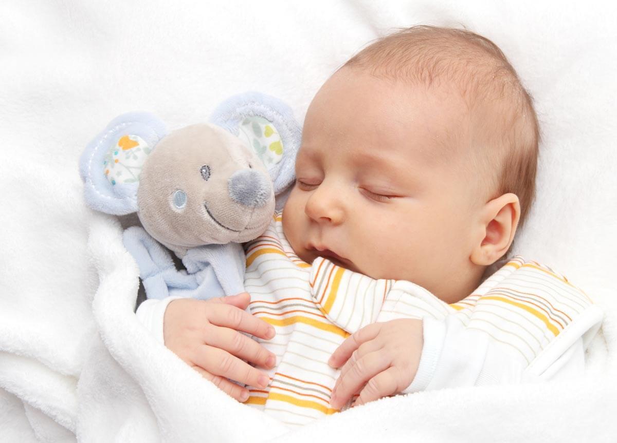 Baby schläft mit warmen Körnerkissen im Arm