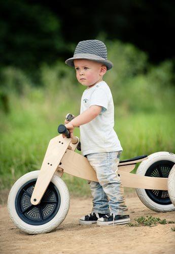 Kleiner Junge mit Holzlaufrad