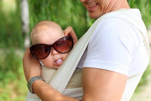 Tragehilfen-Test-Vater-mit-Kind-dass-in-Babytrage-sitz-und-Sonnenbrille-auf-hat