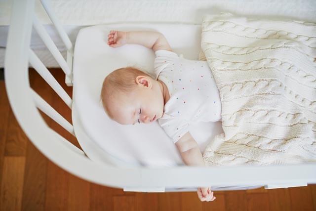 Baby schläft im Beistellbett
