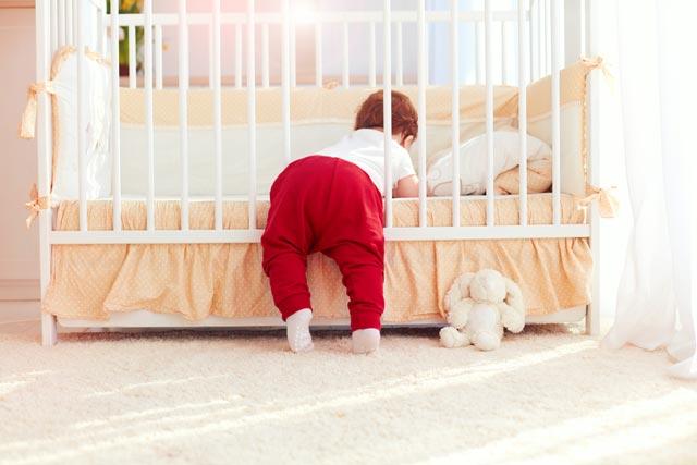 Baby klettert aus Gitterbett