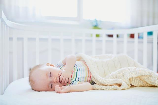 Baby schlaeft im Beistellbett