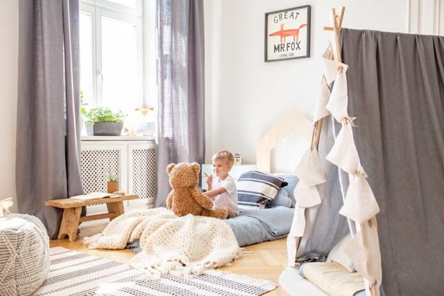 Kind mit Kuscheltier auf Montessori Bett