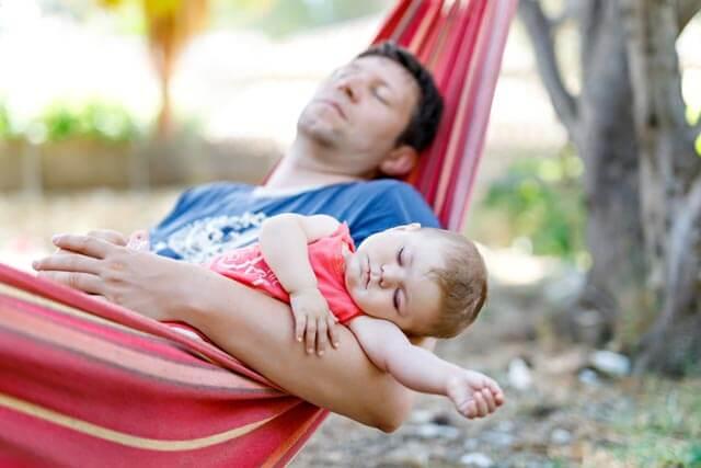 Reisebett: Vater schläft mit Baby in Hängematte