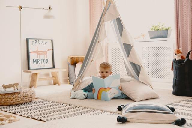 Junge mit Buch im Tipi Bett